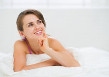Portrait of thoughtful young woman laying on bed. In room Stock Photos