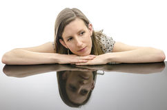 Thoughtful young woman leaning on a table Stock Images