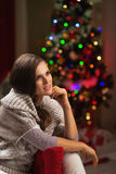Portrait of thoughtful young woman near christmas tree Stock Image