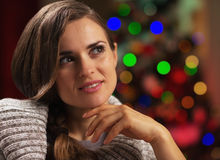 Portrait of thoughtful young woman near christmas tree Royalty Free Stock Image