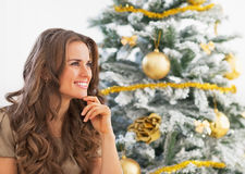 Portrait of thoughtful young woman sitting near christmas tree Royalty Free Stock Photo