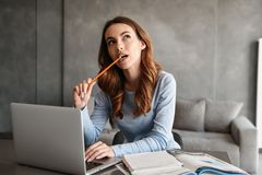 Portrait of a thoughtful young woman studying. While sitting at the table with laptop computer and notebook at home Royalty Free Stock Photography