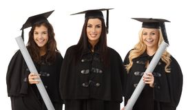 Portrait of three female graduates smiling happy. Portrait of three attractive female graduates smiling happy in academic dress, holding diploma Royalty Free Stock Photos