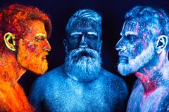 Portrait of three bearded men painted in florescent powders