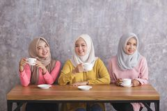 Three beautiful siblings having a coffee time together. Portrait of three beautiful siblings having a coffee time together at coffee shop Royalty Free Stock Photography