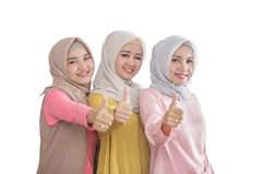 Three beautiful siblings smiling and giving thumbs up. Portrait of three beautiful siblings smiling and giving thumbs up isolated on white background Stock Images