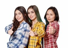 Portrait of three beautiful young happy females smiling joyfully showing thumbs up isolated on white stock photography