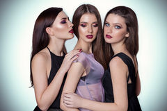 Portrait of three beautiful young women friends in the studio on a white background with yarkis makeup are close to each other. Portrait of three beautiful young Royalty Free Stock Photo