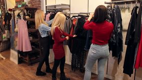 Portrait of three beautiful young women shopping in a clothes shop. stock video