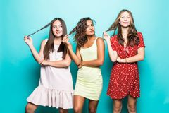 Portrait of Three mixed race best friends posing in studio, wearing summer style dresses against blue wall . Girls smiling and royalty free stock image