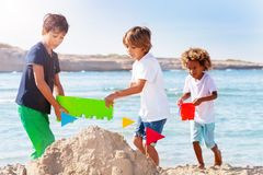 Boys playing at the seaside and making sandcastle. Portrait of three boys making sandcastle, playing at the seaside in summer royalty free stock photos