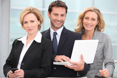 Portrait of three business people outdoors. Three business people outdoors with laptop Stock Photo