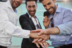 Three businessmen holding hands together in unity gesture Royalty Free Stock Photos