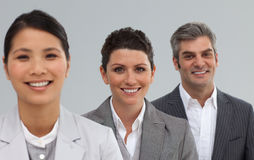 Portrait of three businesspeople smiling. At the camera standing against a white background stock photos