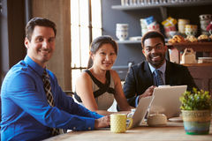 Portrait Of Three Businesspeople Working At Laptop In Cafe Stock Image
