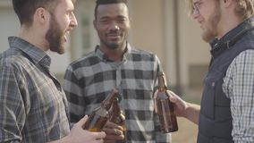 Portrait of three caucasian and african american men standing in the backyard drinking beer. The men clink their bottles. And smiling. Old friends have fun stock video footage