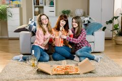 Portrait of three cheerful young female friends with popcorn bowls, pizza and wine, sitting on the floor near the. Stylish sofa at home royalty free stock images