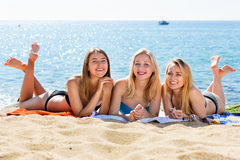 Portrait of three cheerful young women on beach royalty free stock photo