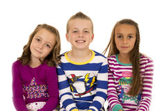 Portrait of three children wearing colorful winter pajamas Royalty Free Stock Images