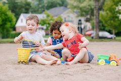 Three cute Caucasian and hispanic latin toddlers babies children sitting in sandbox playing with plastic colorful toys. Portrait of three cute Caucasian and stock photo