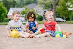 Three cute Caucasian and hispanic latin toddlers babies children sitting in sandbox playing with plastic colorful toys. Portrait of three cute Caucasian and royalty free stock images