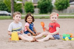 Three cute Caucasian and hispanic latin toddlers babies children sitting in sandbox playing with plastic colorful toys. Portrait of three cute Caucasian and royalty free stock image