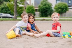Three cute Caucasian and hispanic latin toddlers babies children sitting in sandbox playing with plastic colorful toys. Portrait of three cute Caucasian and stock photos