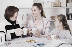 Portrait of three different ages womans. Sitting at the table with cups of tea royalty free stock photos