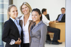 Portrait Of Three Female Executives With Office Meeting In Backg Stock Photos