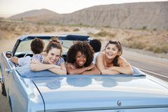 Portrait Of Three Female Friends Enjoying Road Trip In Open Top Classic Car stock photography