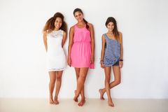 Portrait Of Three Female Friends Leaning Against Wall Stock Photo