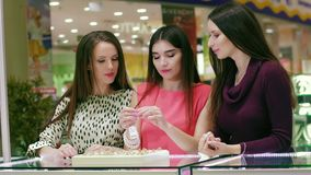 Portrait of three female friends looking and trying on rings in shopping mall stock footage
