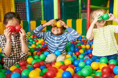 Happy Kids Playing in Ball Pit. Portrait of three funny little kids playing in ball pit and enjoying time in childrens entertainment and play area, copy space royalty free stock image