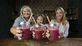 Joyful family drinking fresh berry smoothie stock video footage