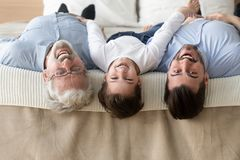 Portrait of three generations of men lying upside down. Portrait of happy three generations of men lying on bed upside down looking at camera smiling, little son stock photography