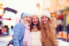 Portrait of three happy girls, friends together on winter street Stock Photos