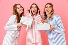 Portrait of three happy girls 20s wearing colorful striped leisu. Re clothing screaming in excitement while holding gift boxes isolated over pink background Stock Photo