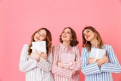 Portrait of three happy girls 20s wearing colorful striped pyjam. As looking upward with gift boxes in hands isolated over pink background Stock Photography