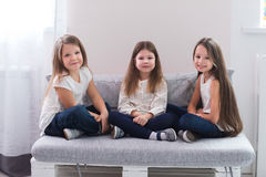 Portrait of three happy girls sitting on sofa and friendship concept Royalty Free Stock Photos