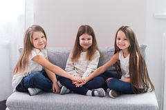 Portrait of three happy girls sitting on sofa and friendship concept Stock Images