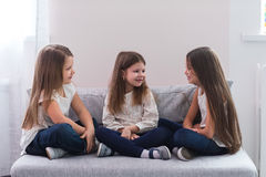 Portrait of three happy girls sitting on sofa and friendship concept.  Royalty Free Stock Image