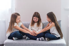Portrait of three happy girls sitting on sofa and friendship concept.  Royalty Free Stock Photos
