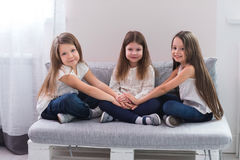 Portrait of three happy girls sitting on sofa and friendship concept.  Stock Photography