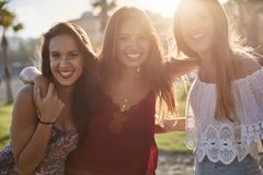 Three happy girls standing together in sunlight smiling Royalty Free Stock Photos