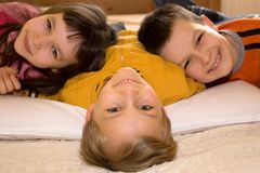 Portrait of Three Happy Kids. A cute portrait of three happy and smiling children lying down Stock Image