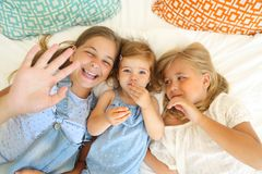 Three happy little sisters on a bed having fun stock photos