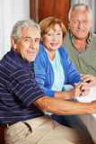 Portrait of three happy seniors. Sitting at table in a rest home Royalty Free Stock Photography
