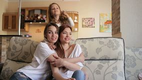 Portrait of three happy sisters on couch at home. Portrait of three happy sisters on the couch at home. Two girls and one little girl play and laugh at home on stock video footage