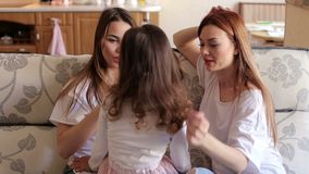 Portrait of three sisters on the couch at home. Portrait of three happy sisters on the couch at home. Two girls and one little girl play and laugh at home on stock video