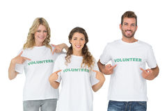 Portrait of three happy volunteers pointing to themselves Royalty Free Stock Images